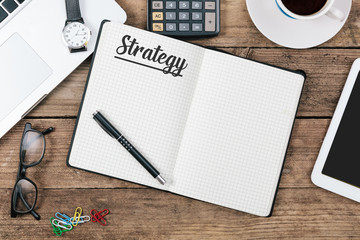 Strategy text on note pad, Office desk with computer technology,