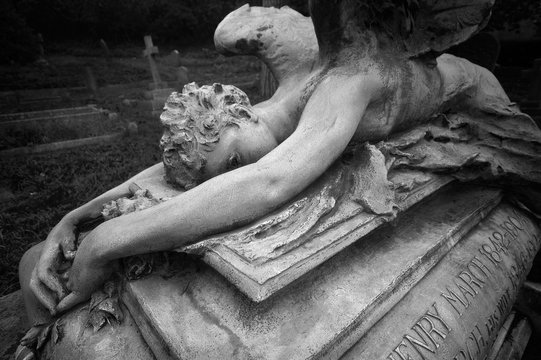 Statue of a weeping angel laying over an ancient grave