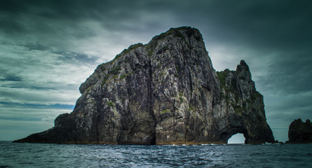 Dramatic view of Hole in The Rock on a stormy day in the Bay of Islands New Zealand