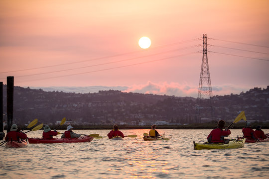 Kayaks on water as sun sets over wetland, marina, and hillsides covered with homes in California