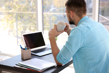 Handsome young man drinking coffee while working with laptop at home