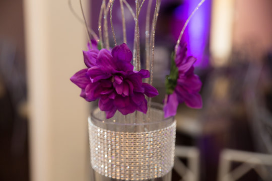 Centerpiece at a party with purple flowers and shiny material
