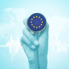 hand holding stethoscope with European Union flag.