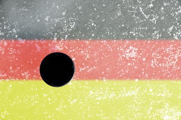 Black hockey puck on ice rink with German flag.