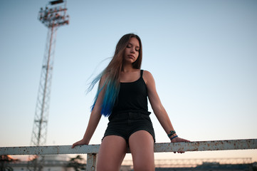 girl with blue hair sitting during sunset