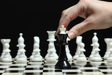 Female hand rearranges the chess piece on the board on a dark background.
