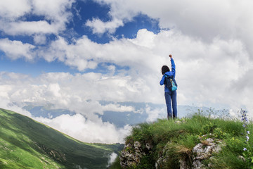 Freedom young traveler girl with hands up in mountains. Victory concept