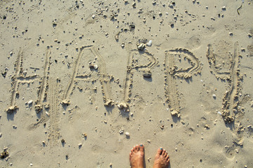 Happy inscription written on white sand beach. Sunny seaside vacation day.