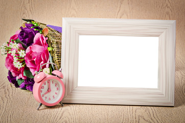 Blank wooden photo frame and pink alarm clock.