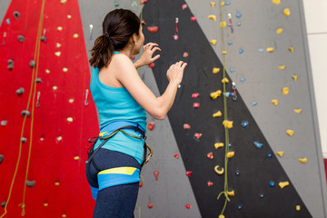Close up of athletic woman standing in a bouldering gym and preparing for climb