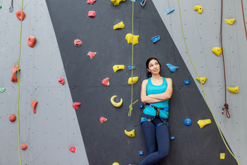 woman coach boulder stands near climbing wall and looking at the camera