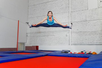 jumping young woman on the trampoline, white brick wall background
