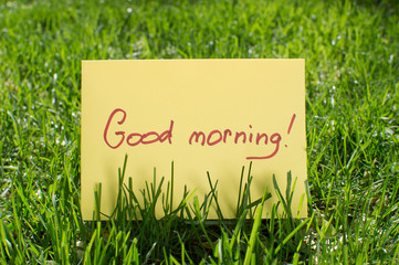 A piece of paper that says good morning lying on green grass in the park. Sunrise. A good day. Good start to the day.