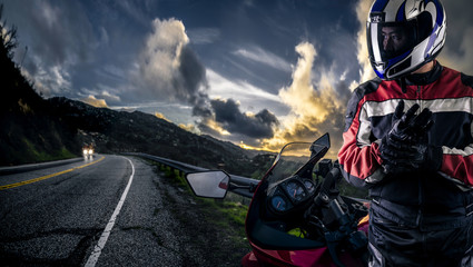 Male motorcyclist wearing protective leather racing suit with a red bike or motorcycle on an open road.  The vehicle is cropped to become generic non branded. The image depicts travel and adventure. Wall mural