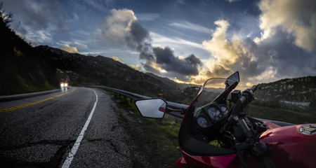 Red street bike motorcycle looking at a cloudy sunset on an open road scenic route. The vehicle is cropped to be generic and non branded. The image depicts motorsports and travel tourism.