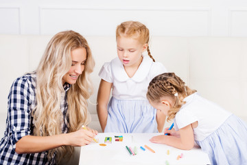 Mother with two beautiful daughters are drawing. Family, motherh