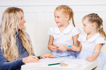 Mother with two beautiful daughters are drawing. Family, motherhood concept.