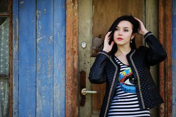 Brunette model girl at leather jacket posed background old woode