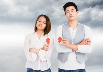 Upset couple holding broken heart