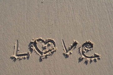 "the word ""love""  in the sand on the beach. Valentine's concept."