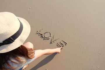 """Woman writing the word """"love""""  in the sand on the beach. Valentine's concept."""