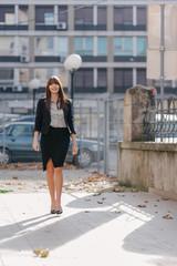 Good-looking businesswoman walking down the yard