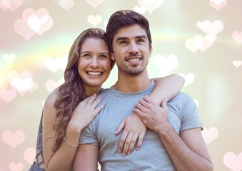 Smiling couple with hearts and rainbow as background