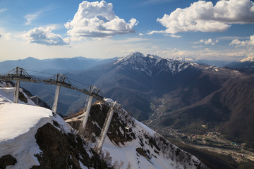 Cable way ski lift on blue sky and snowy mountain peaks scenic background at winter