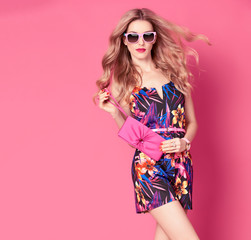 Fashion woman in Trendy Spring Summer Dress. Stylish wavy hairstyle, fashion Sunglasses, Summer Floral Outfit. Glamour Blond lady in Sexy Jumpsuit, fashion pose. Playful Girl,Luxury summer Pink Clutch