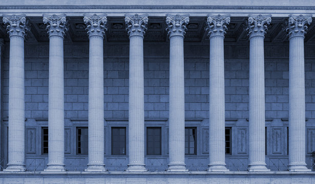 Corinthian columns in a colonnade of a building facade. The neoclassical style resembles a law court / courthouse, university, library or public administration building. Blue color tone.