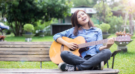 Beautiful young woman playing guitar sitting on bench, Happy tim