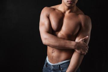 African sportsman posing over black background.