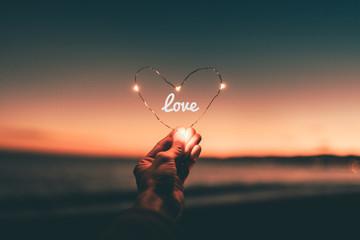 Simbolo del cuore illuminato con scritta love per San Valentino tenuto in mano di fronte al tramonto sul mare.