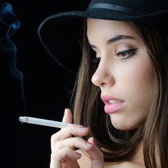 Portrait of the beautiful elegant girl smoking cigarette isolated on black