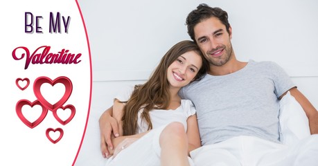 Smiling couple in bed with red heart shapes and valentine text