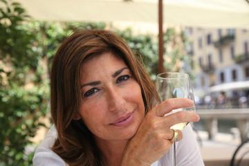 Donna matura sorridente con bicchiere in mano
