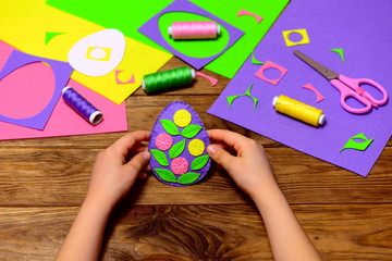 Child holds a felt Easter egg ornament in his hands. Small child made easy Easter crafts. Sewing supplies on a wooden table. How to decorate a felt Easter egg with flowers and leaves