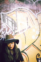 Black female standing near wall with graffiti