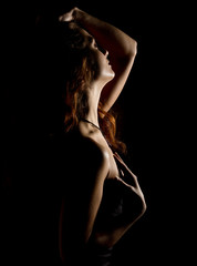 Elegant curves of female shoulders and neck, Redhead girl on a dark background