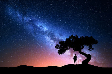 Milky Way. Night sky with stars, old tree and silhouette of a standing alone man on the mountain. Milky way with red light and man on the hill. Galaxy. Silhouette of a man under the tree. Universe