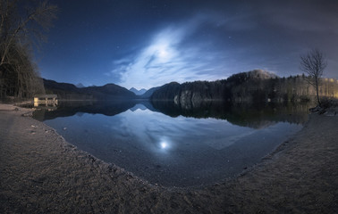 Night in Alpsee lake in Germany. Beautiful landscape with lake, mountains, forest, stars, full moon and clouds reflected in water. Panoramic photo. Spring