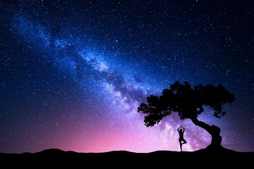 Milky Way with old tree and silhouette of a standing woman practicing yoga. Beautiful landscape with meditating girl under the tree against starry sky with pink milky way. Amazing galaxy. Universe