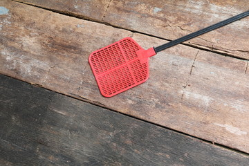 Red fly swatter made of plastic on wood background