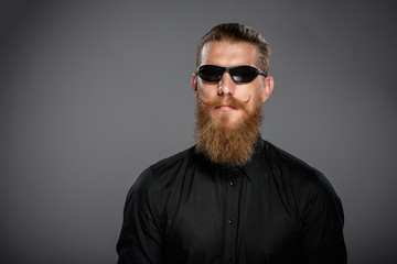 Closeup of hipster man with beard and mustashes wearing black sunglasses, over grey background