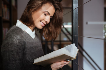 Smiling student girl reading book at library