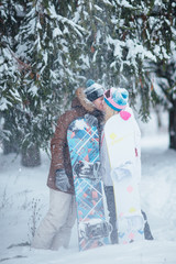 a pair of lovers snowboarders in winter forest