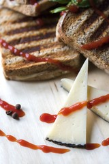 Toasted bread with cheese and ham on a wooden plate decorated with chili peppers, basil and ketchup. Close up.