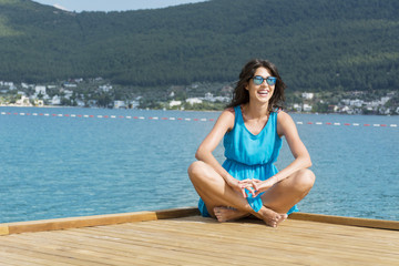 portrait of a beautiful young brunette woman with blue dress sitting on a pier on the beach .Summer holiday