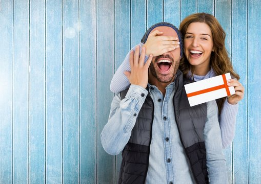 Woman giving surprise gift to man