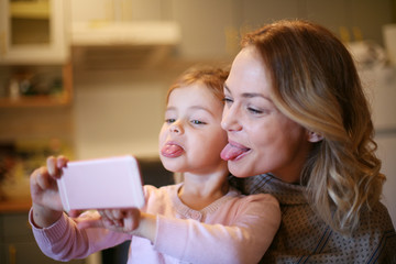 Mother with daughter making funny face.